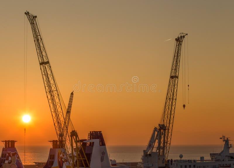 Grúas en astilleros en el puerto de Génova en la puesta del sol, Italia fotografía de archivo libre de regalías