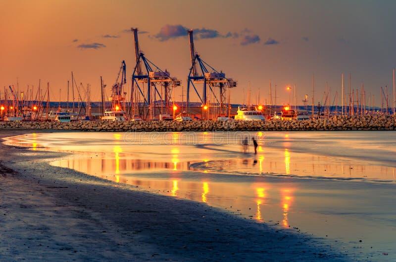 Grúas en la puesta del sol con la playa arenosa y las reflexiones en el primero plano en el puerto de Larnaca, isla de Chipre foto de archivo libre de regalías
