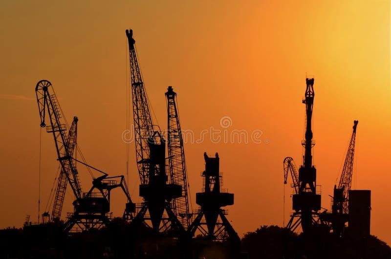 Grúas para los envases cargados sobre los cargueros o buques de carga en el puerto en la puesta del sol imagen de archivo