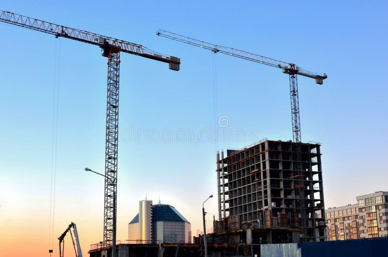 Grúas y siluetas del edificio sobre el sol en la salida del sol Fondo industrial abstracto del cielo azul y imagenes de archivo