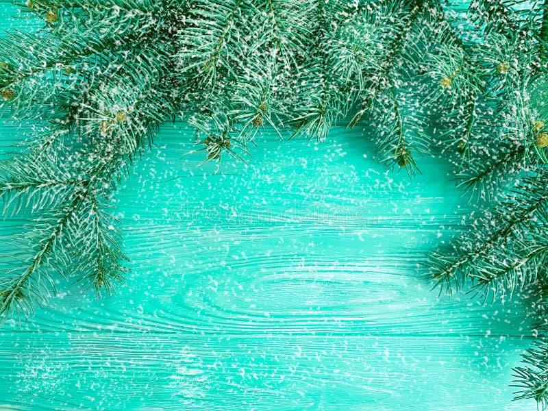 Grüßende dekorative Jahreszeit des Weihnachtsbaum-Winterniederlassungs-Feiertags auf blauem hölzernem Hintergrund, Schnee stockbild