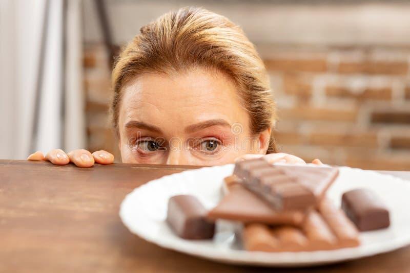 Grünäugige reife Frau, die dunkle Schokolade versteckt und betrachtet lizenzfreies stockfoto