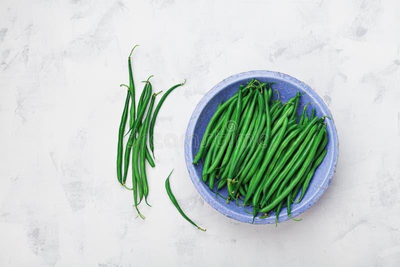 Grün oder Stangenbohnen in der blauen rustikalen Schüssel auf weißer Steintischplatteansicht Biohoflebensmittel stockbilder