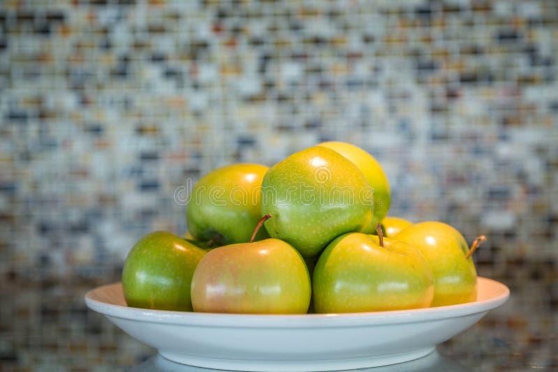 Grüne Äpfel auf weißer Platte stockbilder