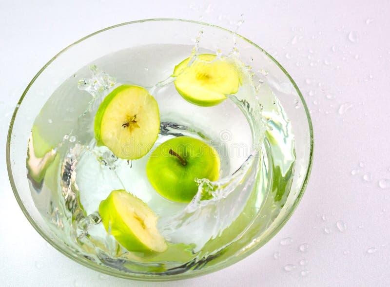 Grüne Äpfel, die in eine Glasschüssel Wasser fallen stockbild