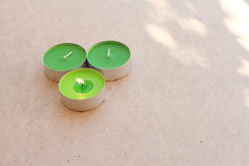 Grüne aromatische Kerzen auf hölzernem Brett mit ihm besitzen Licht stockfotos