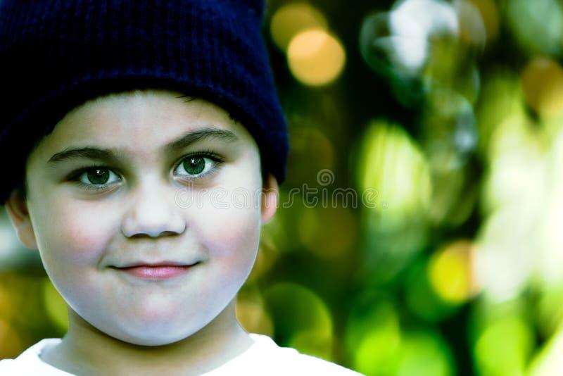 Grüne Augen des Jungen, grüne Hintergrundbüsche lizenzfreie stockbilder