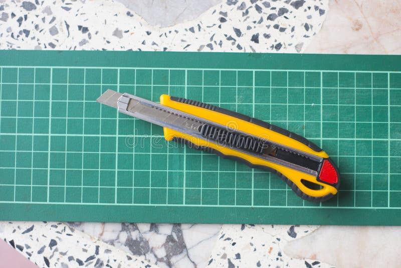 Grüne Ausschnitmatte mit Messer lizenzfreies stockbild