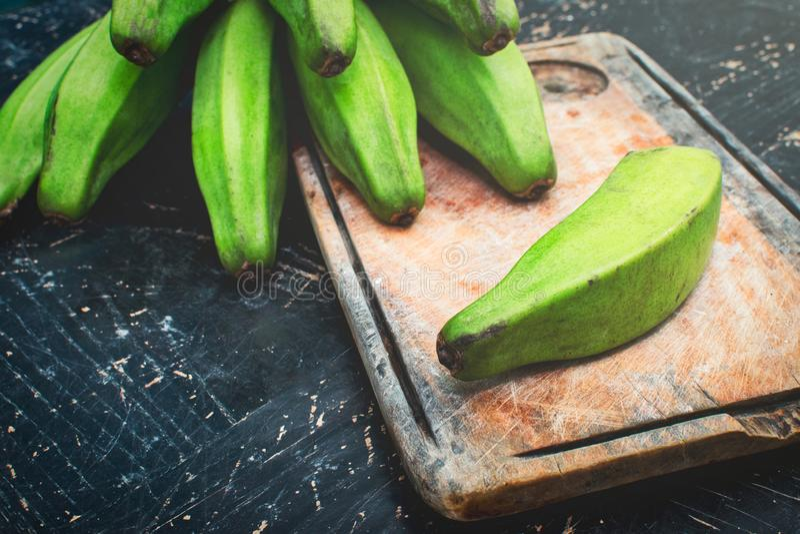 Grüne Banane auf einer rustikalen hölzernen Tabelle stockfotos