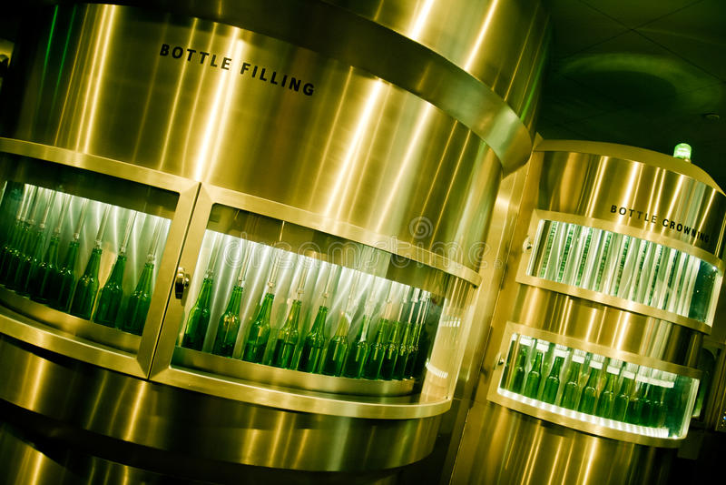 Grüne Bierflaschen, die an der Brauerei gefüllt werden stockbild