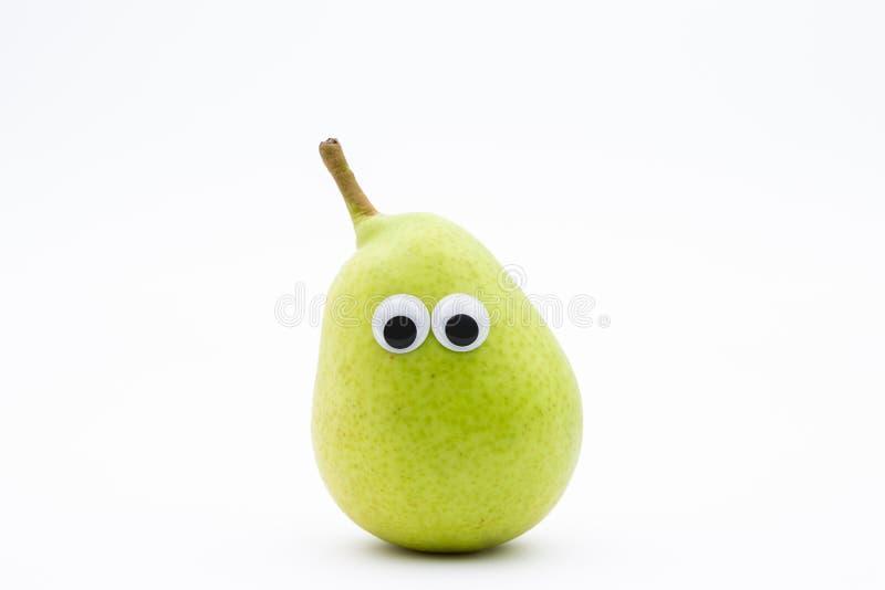 Grüne Birne mit googly Augen auf weißem Hintergrund lizenzfreie stockbilder