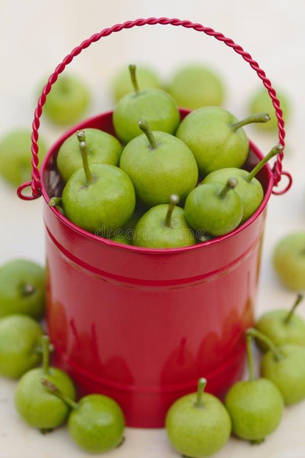 Grüne Birnen im roten Korb auf dem hölzernen Hintergrund lizenzfreie stockbilder