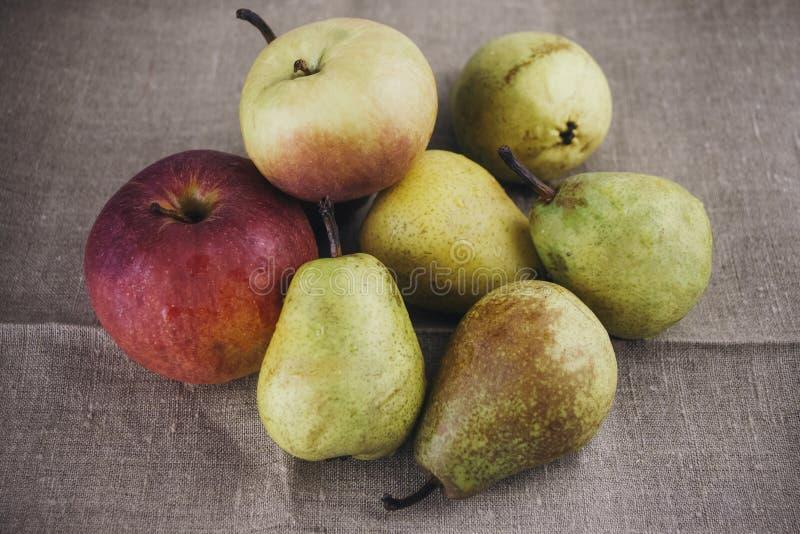 Grüne Birnen und rot-gelbe Äpfel in einer Gruppe stockbild