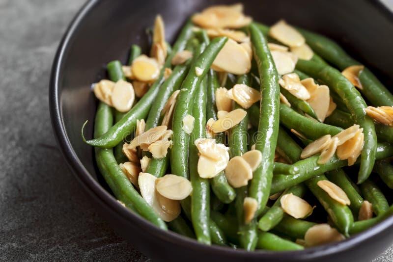 Grüne Bohnen mit gerösteten Mandeln in der schwarzen Schüssel lizenzfreie stockfotografie