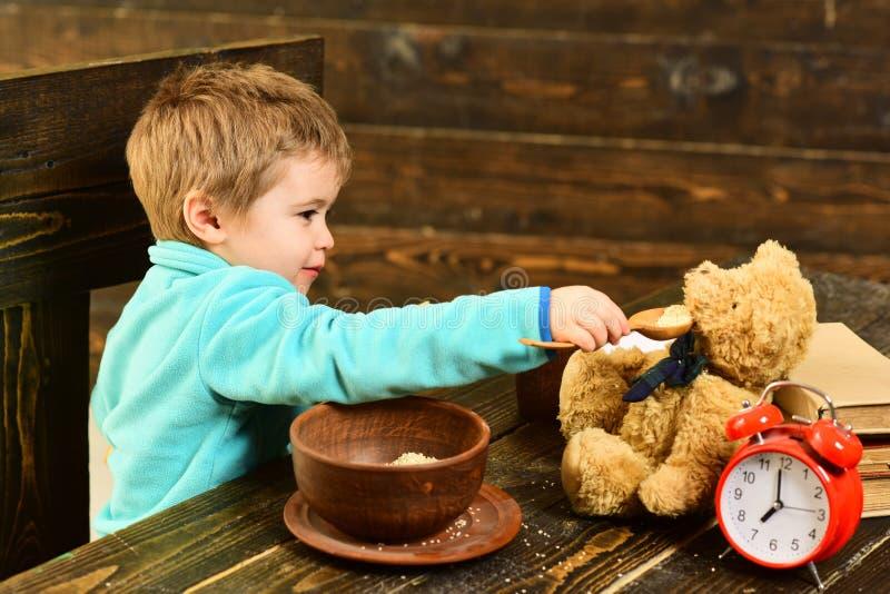 Grüne Borduhrplatte auf Weiß Kleines Kind und Teddybär haben Mahlzeit zusammen Jungenzufuhr-Spielzeugfreund mit gesunder Mahlzeit lizenzfreie stockfotos