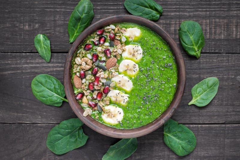 Grüne Detoxfrühstück Smoothieschüssel überstieg mit Granola-, Bananen-, Granatapfel-, Kürbis- und chiasamen lizenzfreie stockfotos