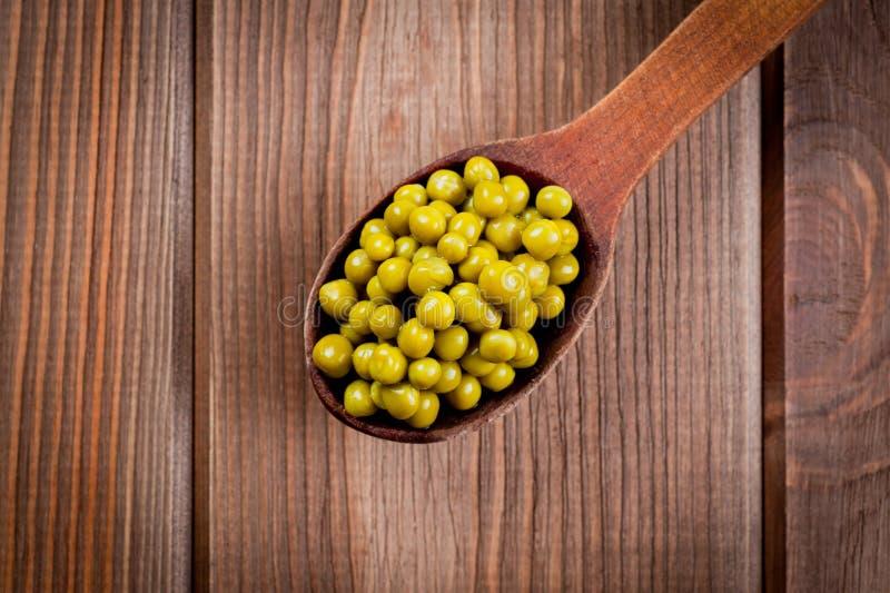 Grüne Erbsen in Dosen in einem Holzlöffel, der auf einer Holzdecke am Tisch liegt stockfoto