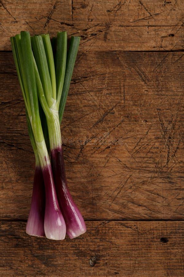 Grüne Frühlingszwiebeln auf Holztisch stockbilder
