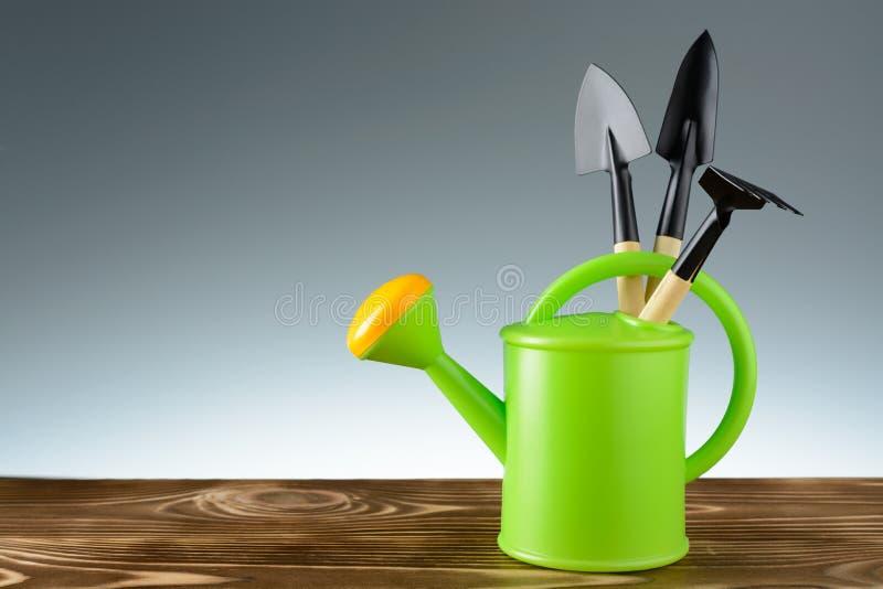 Grüne Gartengießkanne mit Werkzeugen stockbilder