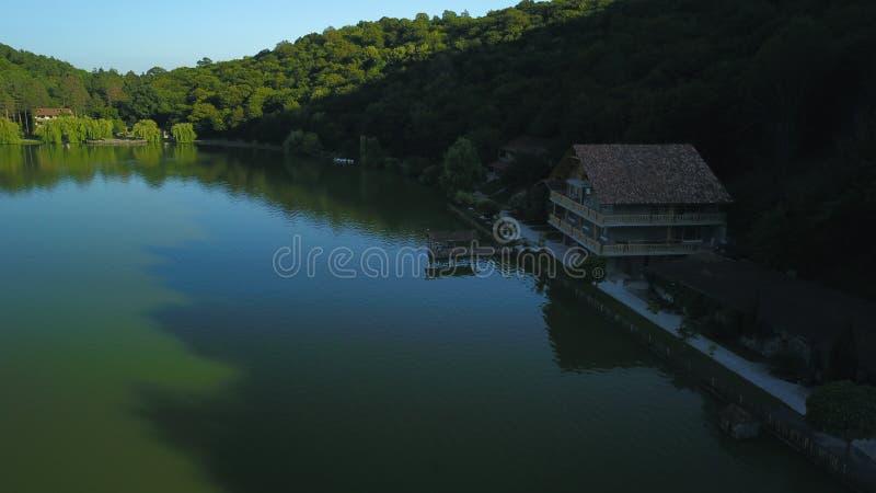 Grüne Gebirgsreflexionen auf blauem ruhigem See stockfoto