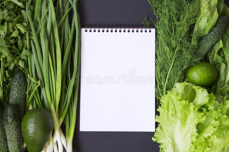 Grüne Gemüse- und Fruchthintergrundavocado, Kalk, Kohl, Petersilie, Gurke, Dill, Zwiebel, Salat, Spinat mit Notizbuch stockfoto