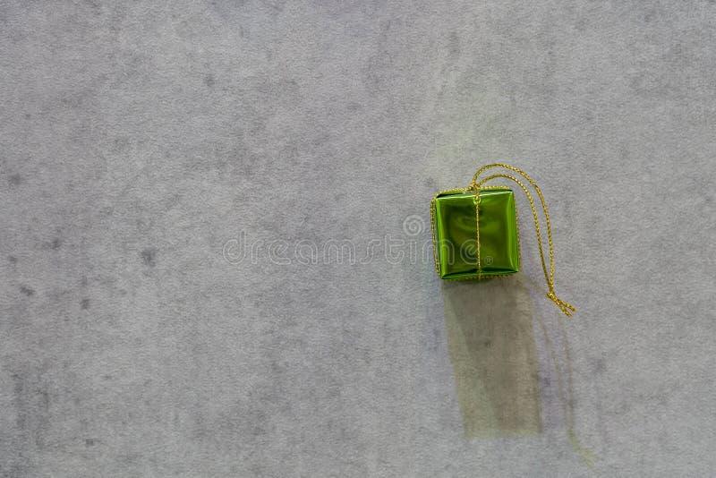 Grüne Geschenkbox mit Gray Cemented Background lizenzfreies stockfoto