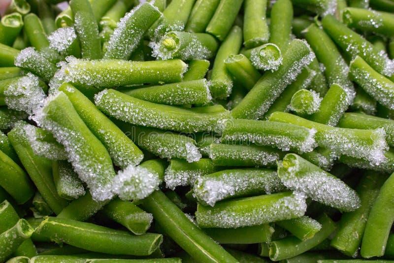 Grüne geschnittene Bohnen mit gefrorenem Gemüse des Frosts Grüne gehackte Gartenbohnenahaufnahme lizenzfreie stockfotos