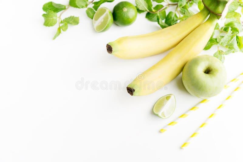Grüne gesunde Getränkbestandteile auf weißem Hintergrund: Kalk, Apfel, Banane, frische Minze und bunte Papierstrohe Vegetarische  stockbild