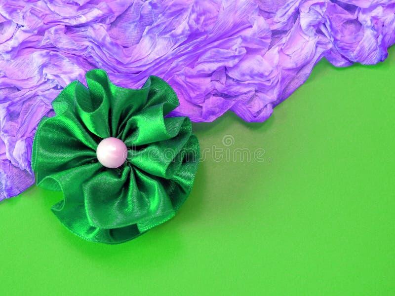 Grüne Gewebeblume auf grünem und violettem Hintergrund stockfotografie