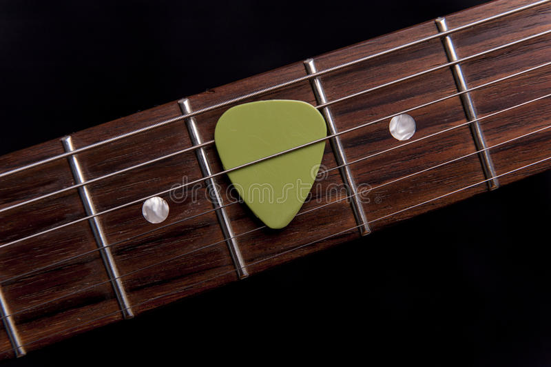 Grüne Gitarren-Auswahl auf dem Fingerboard lizenzfreies stockbild