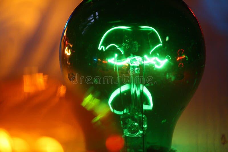 Grüne glühende Birne mit gelbem Hintergrund lizenzfreie stockfotos