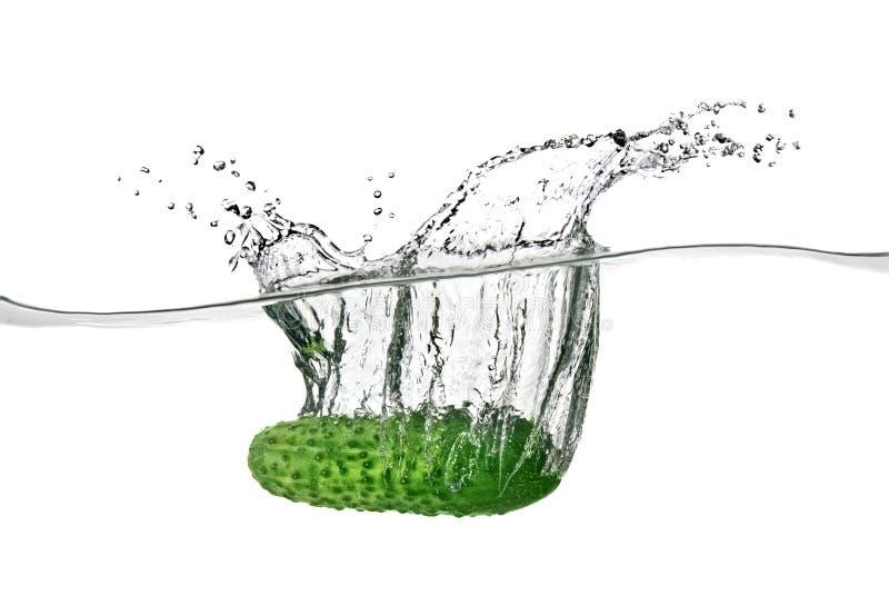 Grüne Gurke fiel in Wasser lizenzfreie stockbilder
