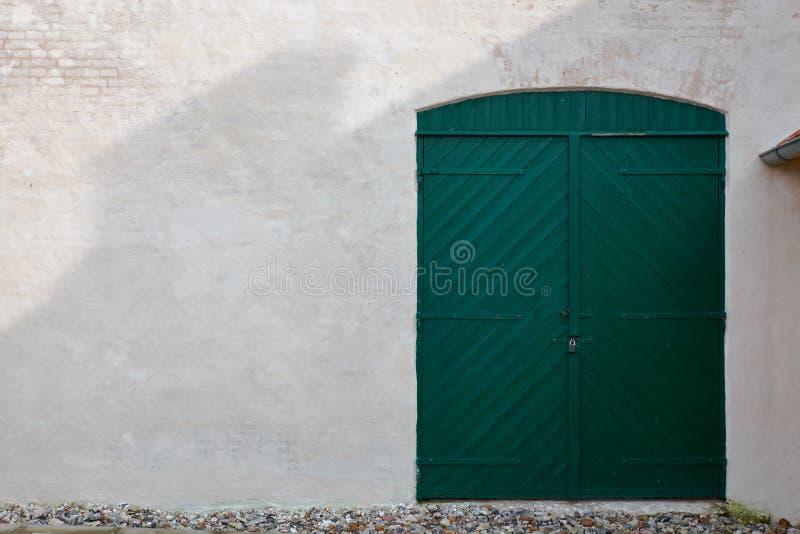 Grüne hölzerne Scheunentür in der Backsteinmauer stockbilder
