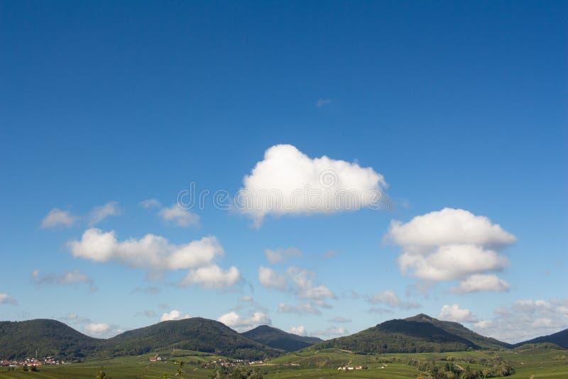 Grüne Hügel unter einem klaren blauen Himmel mit weißen Wolken stockfoto
