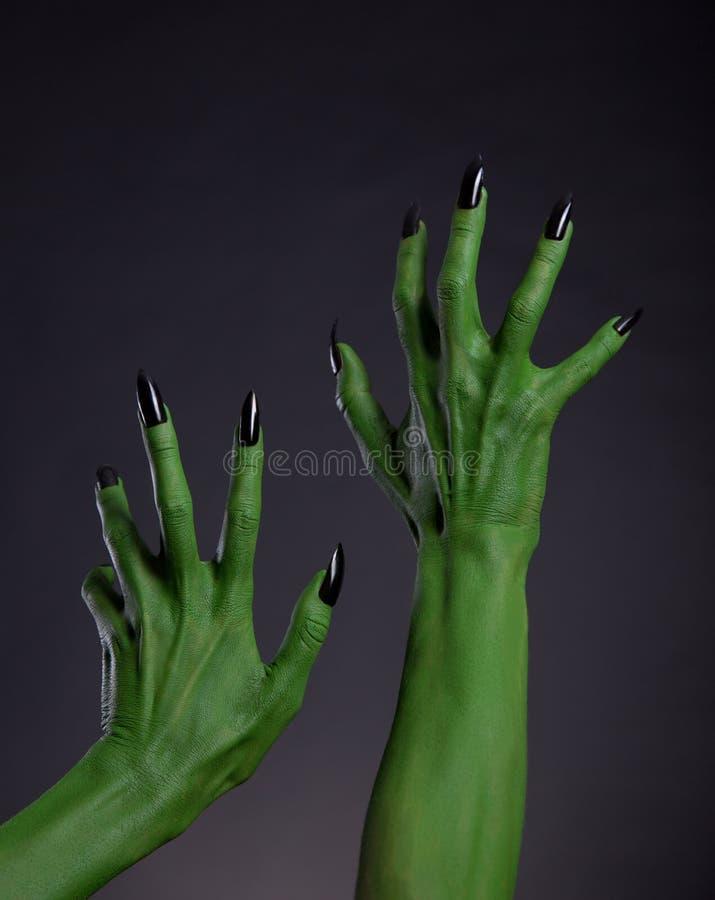 Grüne Hexenhände mit den schwarzen Nägeln, die oben, wirkliche Körperkunst ausdehnen stockfotografie