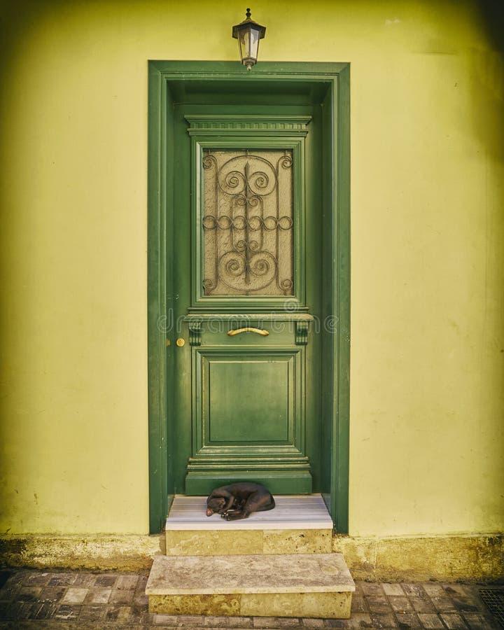 Grüne Holztür der Weinlese auf gelber Haustür lizenzfreie stockfotografie