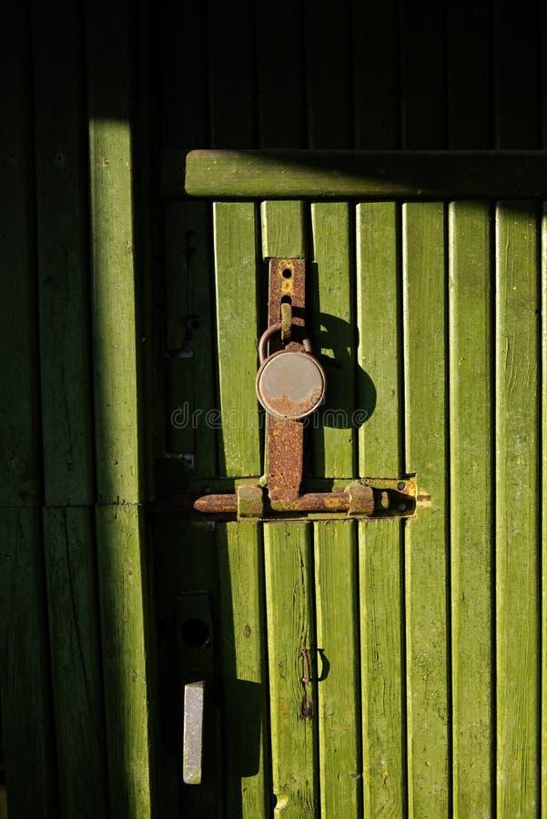 Grüne Holztür mit Schlüsselverschluß stockbild
