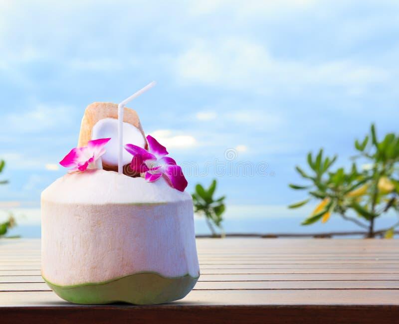 Grüne Kokosnuss- und Orchideenblumen als Begrüßungsgetränk in tropischem De lizenzfreie stockbilder
