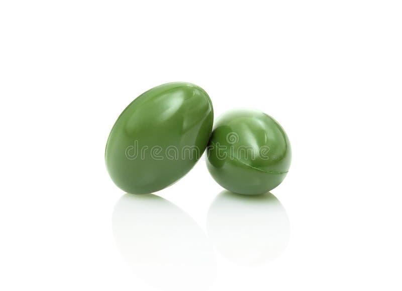 Grüne Kräuterergänzungskapsel lokalisiert auf weißem Hintergrund lizenzfreie stockbilder