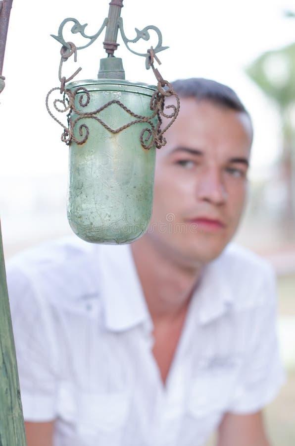Grüne Lampe auf dem Hintergrund eines Mannes in einem weißen Hemd lizenzfreie stockfotografie