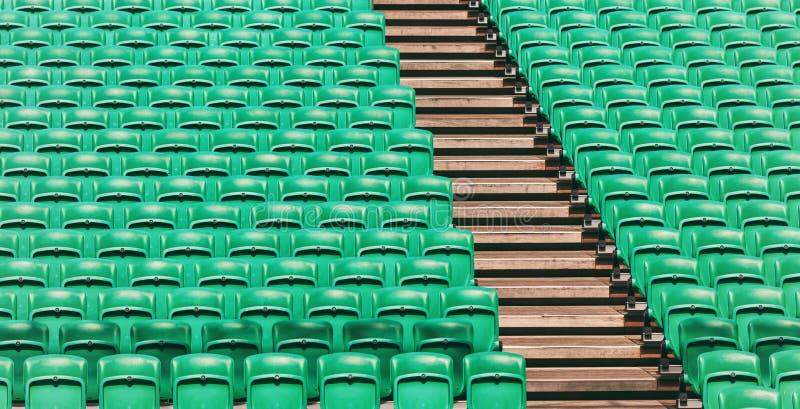Grüne leere Stadionsklappsitze und hölzerne Treppe lizenzfreie stockbilder