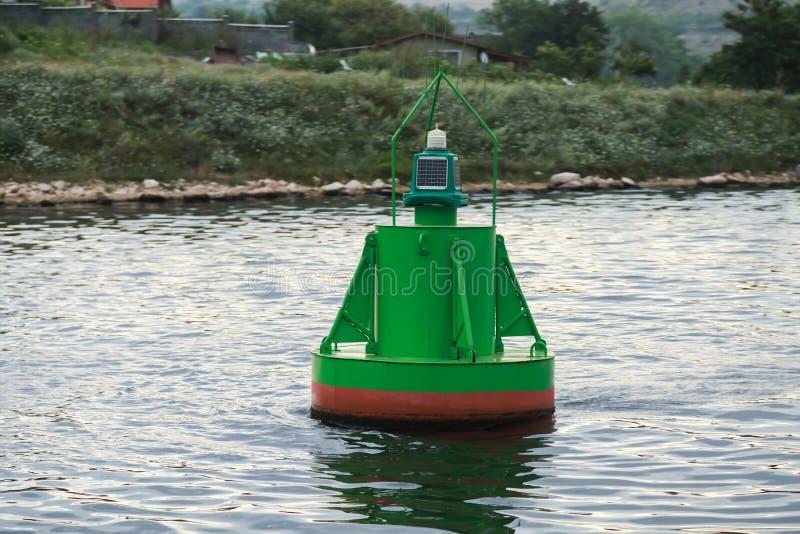 Grüne Navigationsboje, die auf Meerwasser schwimmt lizenzfreie stockfotografie