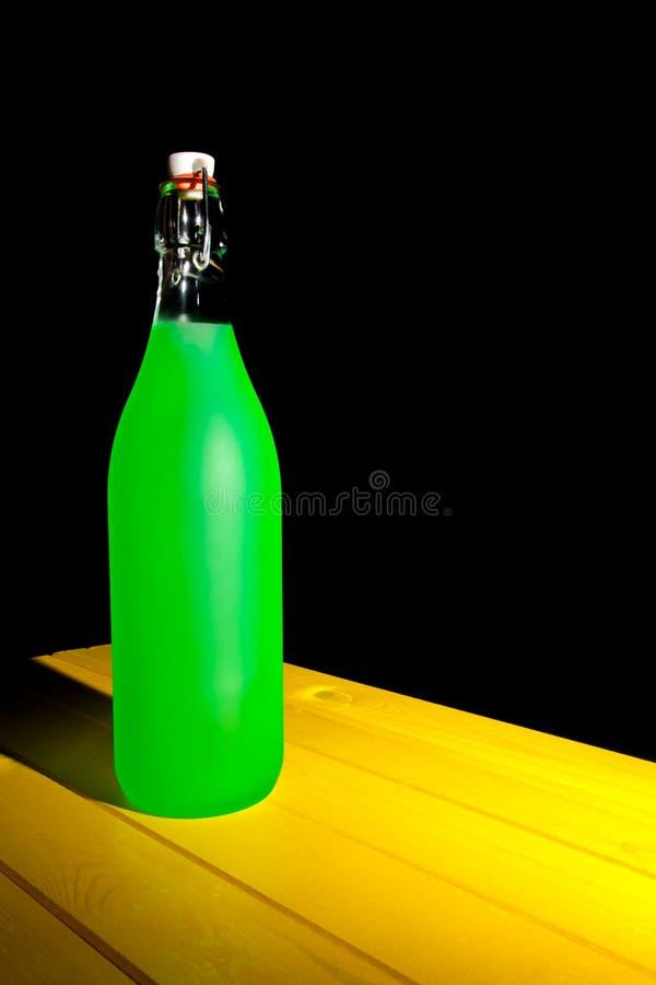 Grüne Neonflasche auf gelber Tabelle Painterly Fantasiestillleben lizenzfreie stockbilder