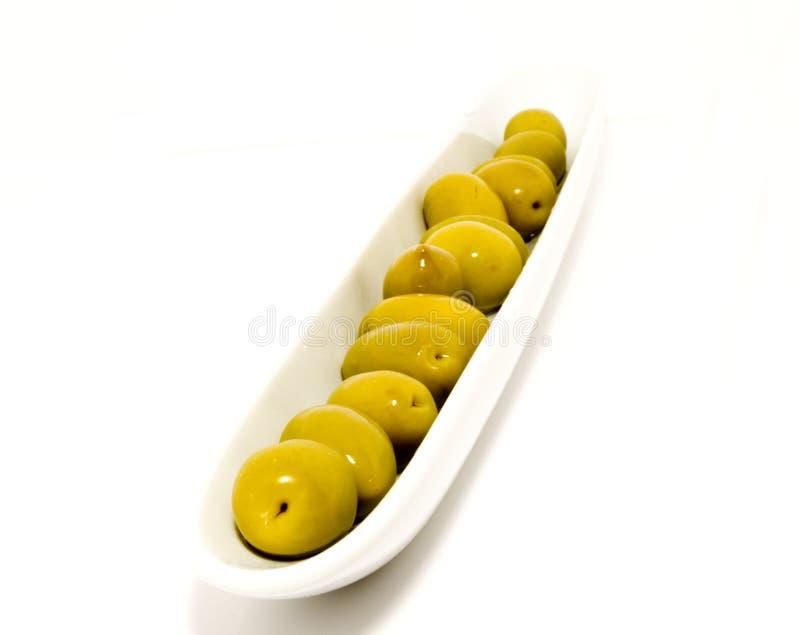 Grüne Oliven in einer Boot-geformten Platte stockfotos