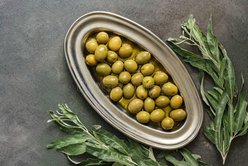 Grüne Oliven im Olivenöl, Metallplatten-, dunkler rustikaler Hintergrund, verziert mit Blättern Draufsicht, flache Lage, Kopienra stockfotografie