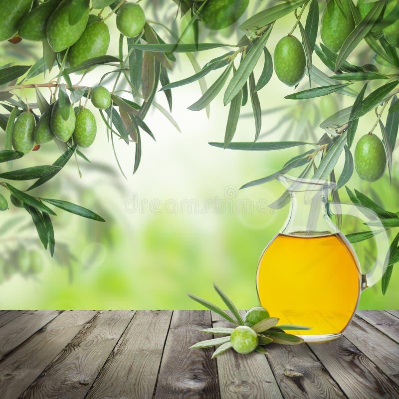 Grüne Oliven, Olivenölflasche, abstraktes bokeh Licht lizenzfreie stockfotografie