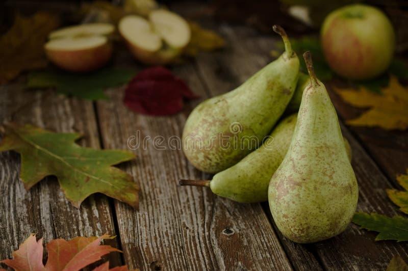 Grüne organische Birnen und Äpfel auf rustikaler hölzerner Tabelle lizenzfreie stockbilder