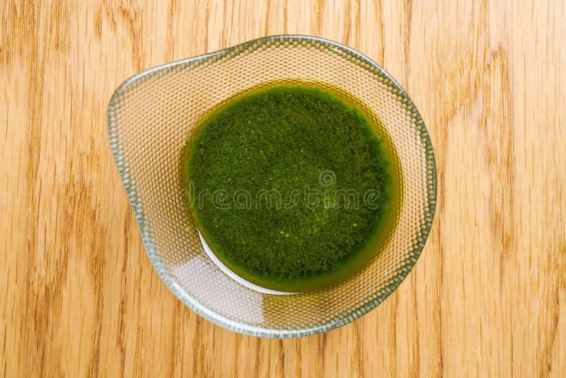 Grüne Pestosoße lokalisiert auf hölzernem Hintergrund, Draufsicht Pesto sause gedient in der Glasschüssel lizenzfreie stockfotografie