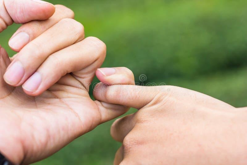 Grüne Pfeile auf Grey Background Indicate die Richtung Schließen Sie herauf Hände von den Paaren, die ` s L sich haken stockfotografie