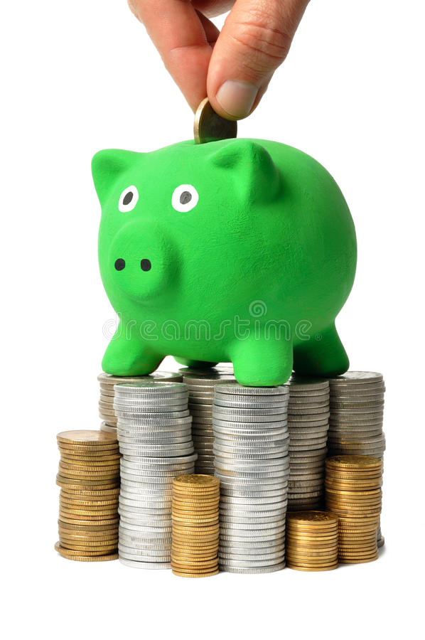 Grüne Piggy Querneigung und Münzen lizenzfreie stockfotos